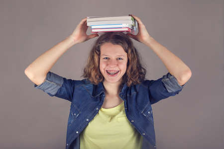 Young smiling curly hair girl with braces on teeth holds books on her head. 写真素材