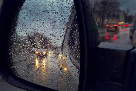 Reflection of cars with headlights on in the wing mirror of a car with raindrops. Reflection of cars with headlights on in the wing mirror of a car with raindrops. Car traffic on a city street in the rain.