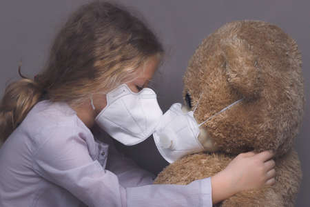 Little girl in a medical mask hugs a teddy bear in a medical mask.