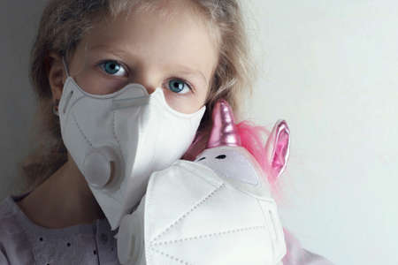 Little girl in a medical mask hugs a unicorn in a medical mask. 写真素材
