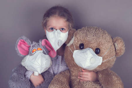 Little girl in a medical mask hugs a soft toys in a medical mask. 写真素材