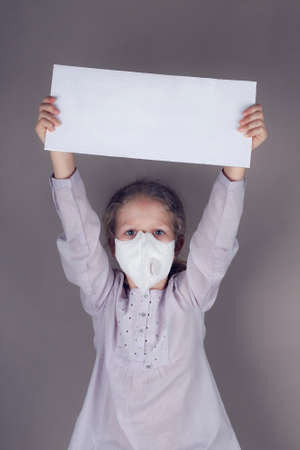 Little girl in medical mask is holding blank white poster on a gray background.