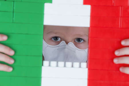 Little girl in a respirator looks out the window in the blocks toy of colors of the Italian flag. Self isolation concept, stay at home.