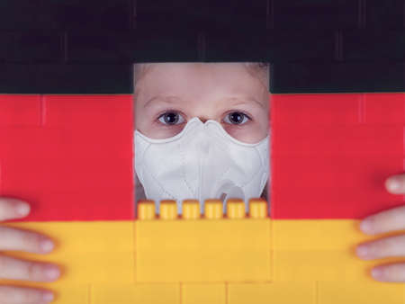 Little girl in a respirator looks out the window in the blocks toy of colors of the German flag. Self isolation concept, stay at home.
