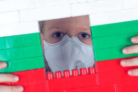 Little girl in a respirator looks out the window in the blocks toy of colors of the Bulgarian flag. Self isolation concept, stay at home. 写真素材