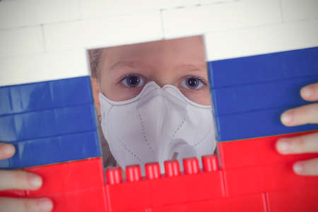 Little girl in a respirator looks out the window in the blocks toy of colors of the Russian flag. Self isolation concept, stay at home.