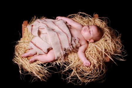 The Baby Jesus swaddled and lying in the manger Stock Photo