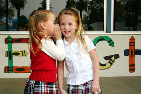 naughty or nice: Two pretty little girls telling secrets and giggling in the schoolyard Stock Photo