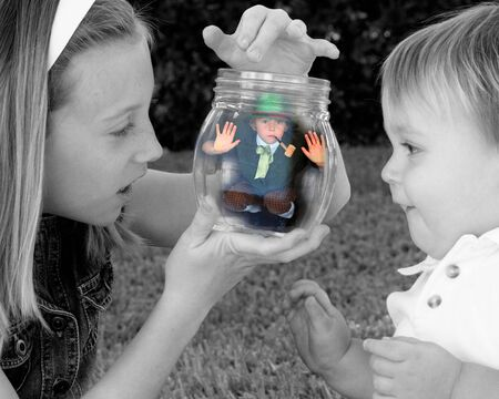 Two adorable children staring in wonder at the leprechaun they have caught in a jar Stock Photo