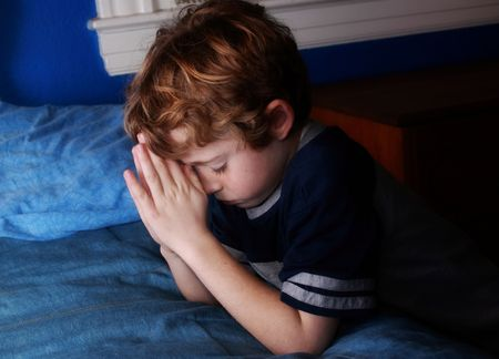 prayer: young boy kneeling before his bed to say his prayers Stock Photo