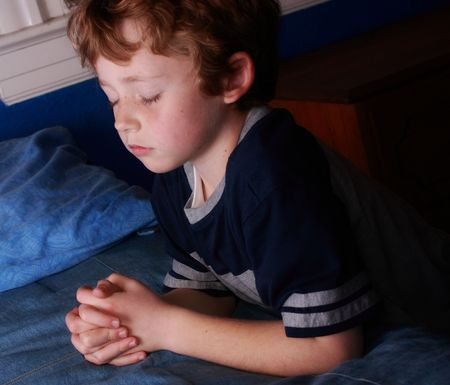 young boy kneeling before bed praying Stock Photo