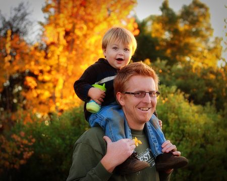 father carrying toddler piggyback against fall colors