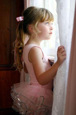 window curtains: ballerina child looking through bedroom window Stock Photo