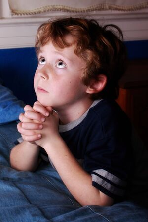 young boy saying his bedtime prayers Stock Photo