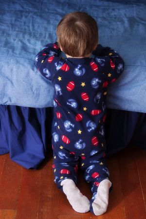 baby kneeling before his bed in prayer Stock Photo