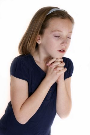 young girl with hands clasped in prayer photo