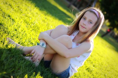 pretty little girl sitting in the grass Stock Photo