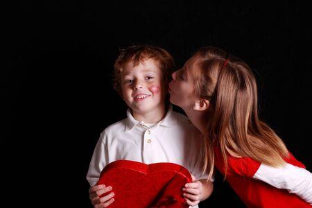 little Valentine boy getting his first kiss photo