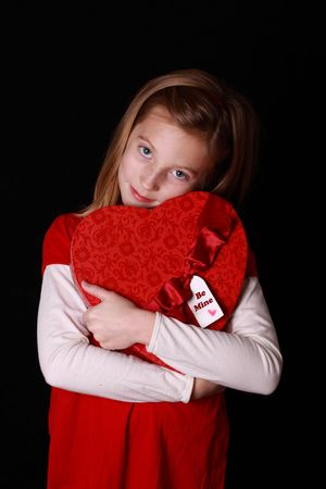 shy little girl holding a large valentine heart photo