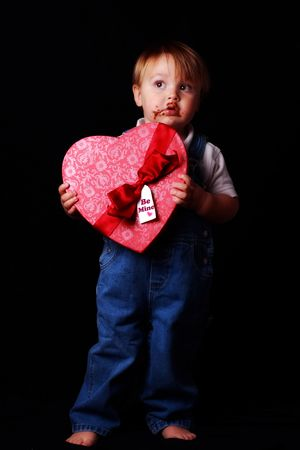 guilty toddler holding a valentine with chocolate on his face photo