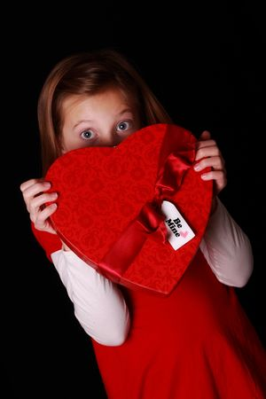 shy little girl hiding behind a heart shaped valentine photo