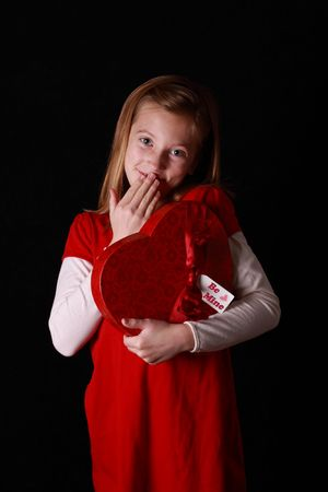 embarrassed little girl giggling and holding a heart shaped valentine photo