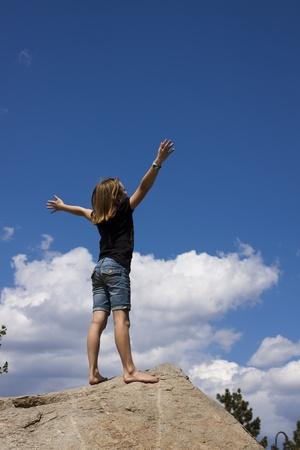 alabando a dios: Ni�a antes de un cielo azul con armas en adoraci�n