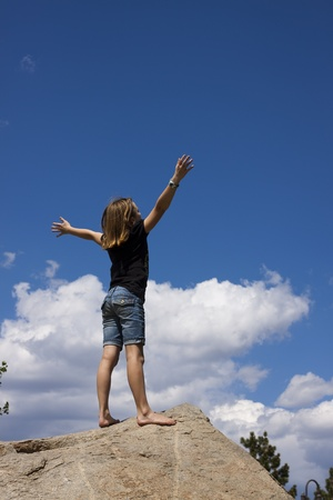 Young girl before a blue sky with arms raised in worship photo