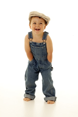adorable toddler in overalls and a vintage hat Archivio Fotografico