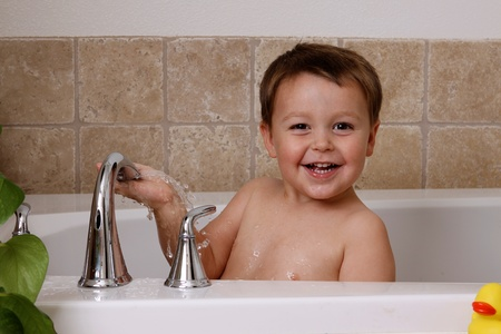 happy toddler playing in bath tub
