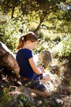 arrodillarse: niña rezando en un hermoso escenario woodsy