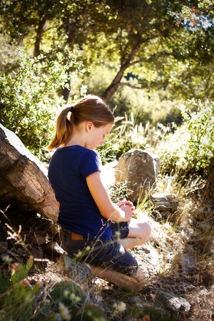 young girl praying in a beautiful woodsy setting Stock Photo