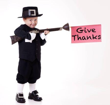 Adorable pilgrim child with rifle, giving thanks