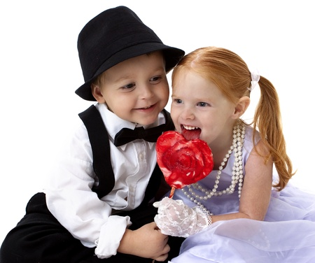adorable little boy and girl sharing a heart shaped sucker Stock Photo