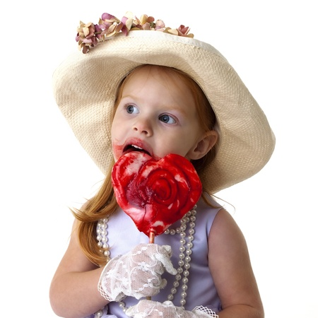 adorable little girl all dressed up with a giant heart shaped lollipop Stock Photo