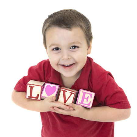 Adorable little boy holding blocks that spell out love