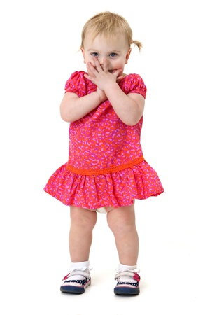 pretty little girl covers her face in embarrassment