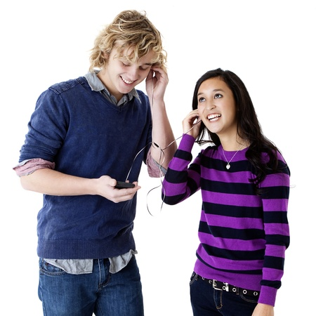 teen couple listening to music on shared headphones photo