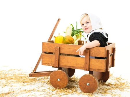 pilgrim costume: pretty baby girl dressed in Pilgrim costume sitting in a wagon with her harvest produce  Stock Photo
