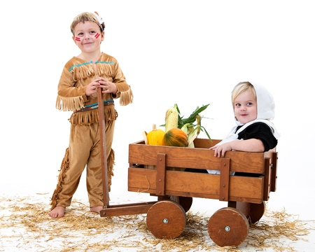 indian boy: adorable boy and girl dressed as a pilgrim and indian sharing their harvest Stock Photo