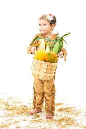 adorable little boy dressed as a Native American holding a basket of harvest vegetables  photo