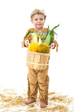 indian thanksgiving: adorable little boy dressed as a Native American holding a basket of harvest vegetables