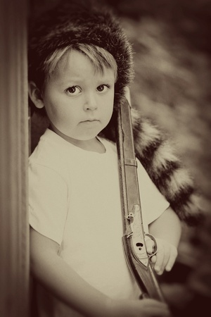 vintage gun: vintage child with toy rifle and coonskin cap