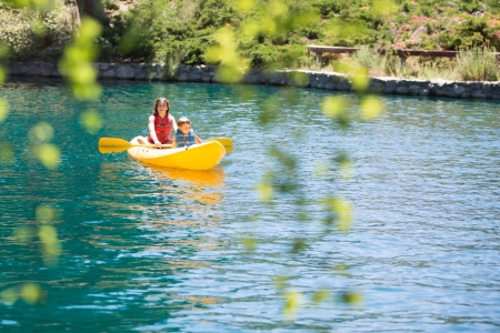 A young girl and boy Kayaking in a Mountain Lake Stock Photo