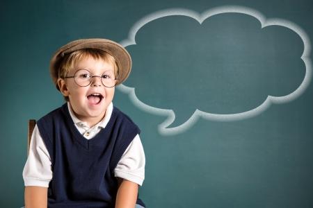 Adorable school boy with speech bubble and chalkboard Archivio Fotografico