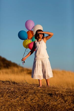 Pretty young woman holding colorful balloons and shading her eyes from the sun