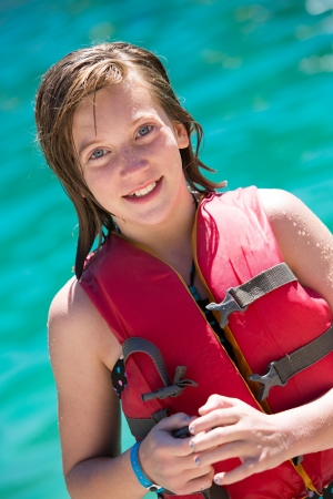 Teen girl wearing life vest in front of a lake