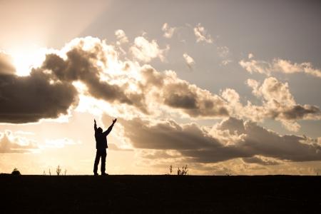 silhouet van een man met opgeheven armen in aanbidding