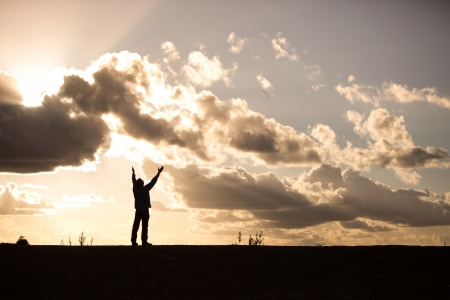 praise: silhouette of a man with arms raised in worship