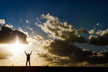 A man with arms raised worshipping before a beautiful sky
